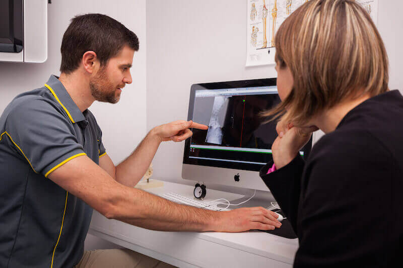 Doctor Is Showing Osteopath Report To Their Patients On Computer